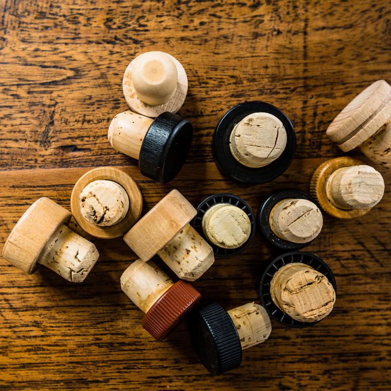 Korken auf einem Holztisch: Die Idea Distillers unterstützen Sie bei der Distribution Ihrer Spirits.
