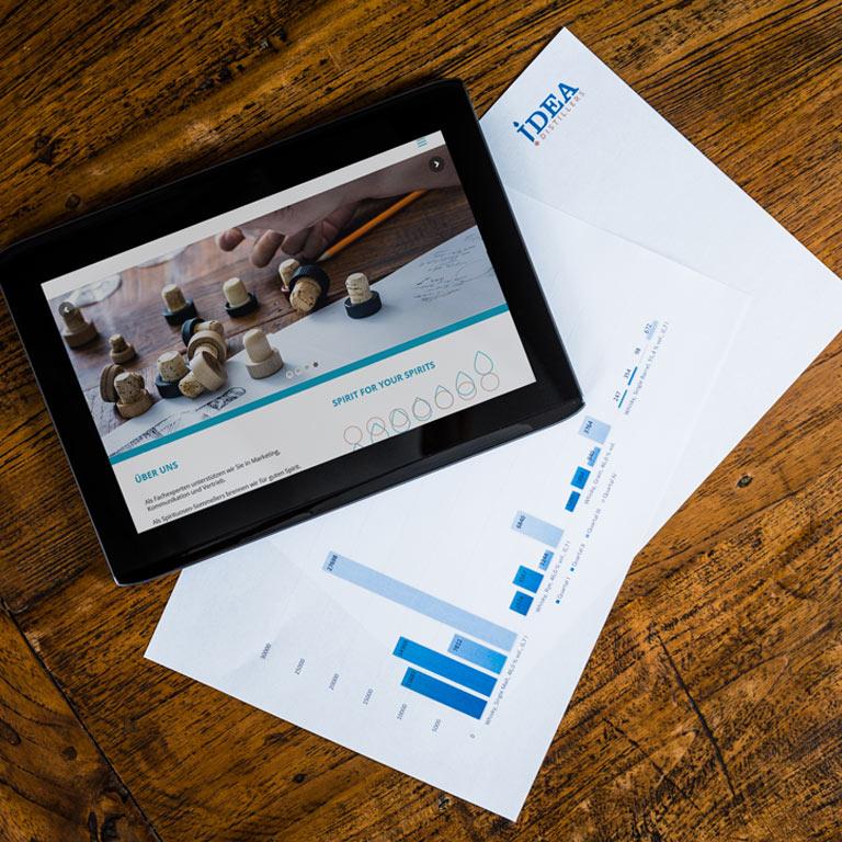 Tablett und Statistiken auf einem Holztisch: Die Idea Distillers bieten Unterstützung im Bereich Online und Social Media.