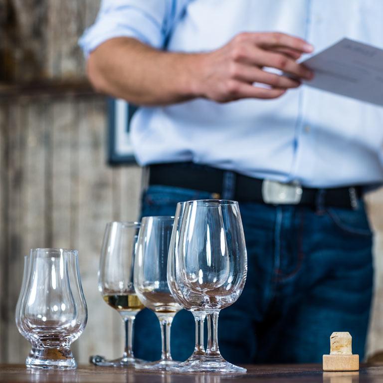 Gläser auf einem Holztisch, eine Person im Hintergrund: Die Idea Distillers unterstützen Sie im Eventmanagement.