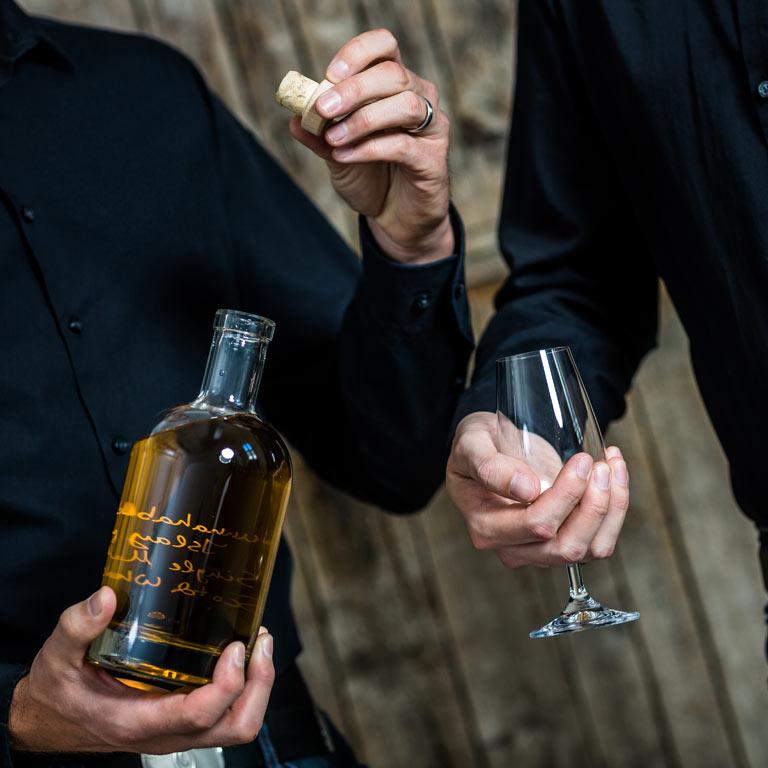 Eine Whiskyflasche und ein leeres Glas werden in die Kamera gehalten, kurz vor dem Eingießen.