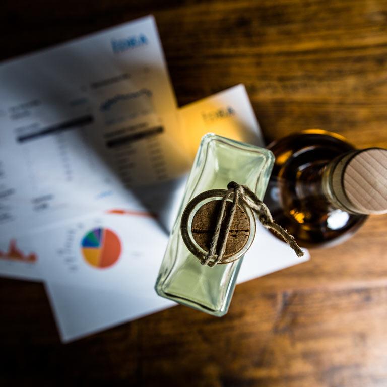 Sicht auf zwei Flaschen und Papiere auf einem Holztisch: Die Idea Distillers unterstützen Sie im Vertrieb Ihrer Spirituosen.
