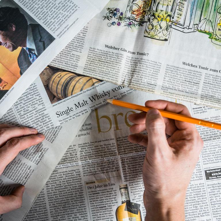 Stift wird über Zeitungen gehalten: Bekanntheit erhöhen, Image aufbauen mit den Idea Distillers.