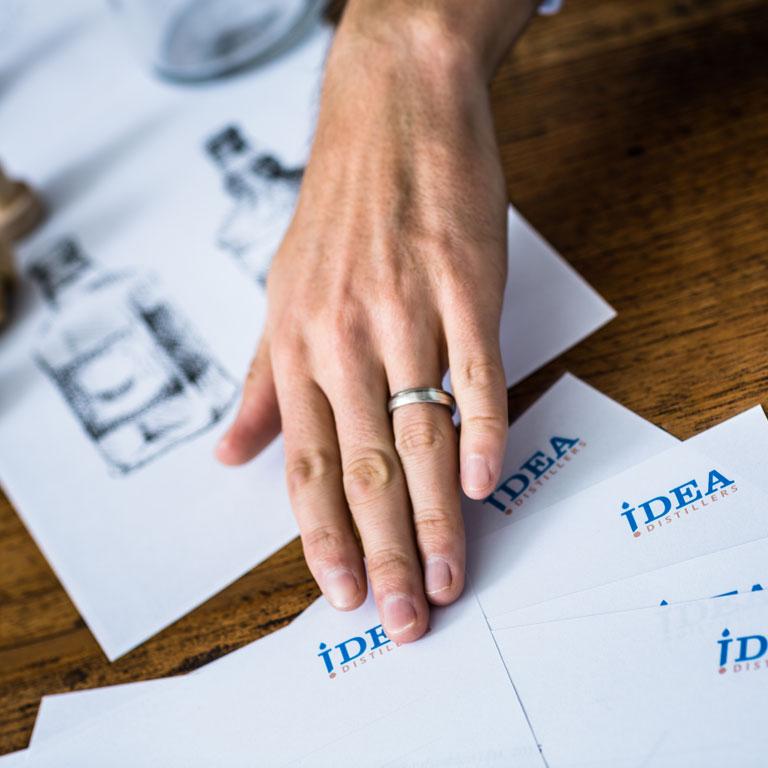 Hand und Zettel auf Holztisch: Kostenlose Erstberatung zu Ihren Spirits bei den Idea Distillers.