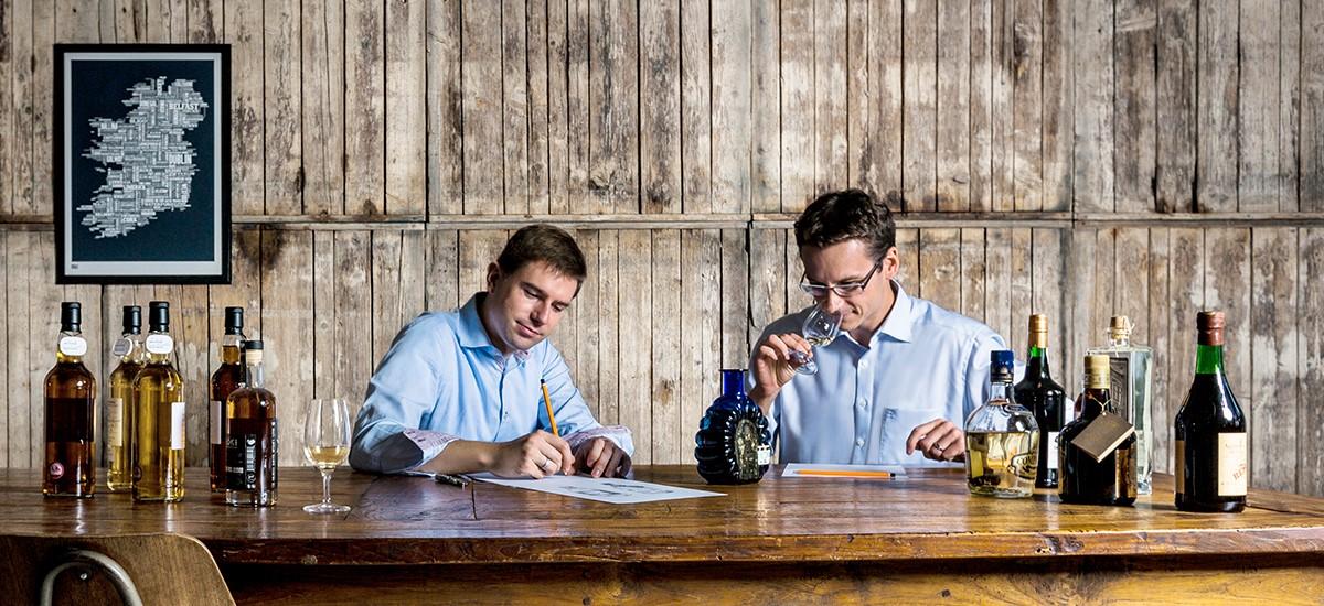 Die Idea Distillers Simon Weiß und Christian Schrade bei der Arbeit an einem Holztisch.