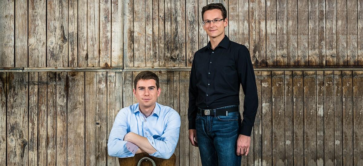 Die Geschäftsführer der Idea Distillers Christian Schrade und Simon Weiß vor einer Holzwand