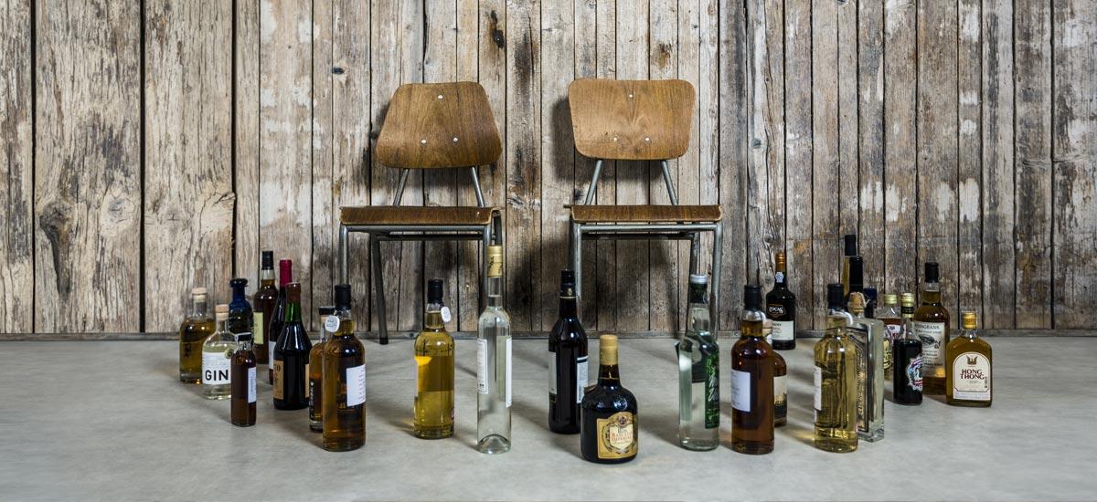 Zwei leere Stühle und viele Flaschen mit hochwertigen Spirituosen: Jobs im Team der Idea Distillers.