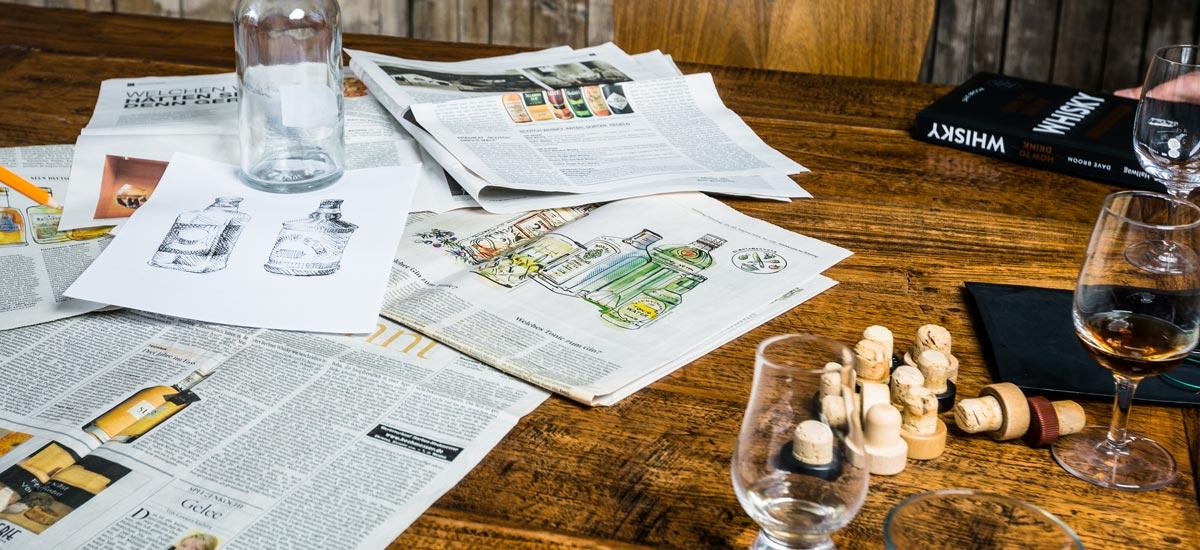 Tisch mit Zeitungen und Whisky: ein Arbeitstag bei den Idea Distillers.