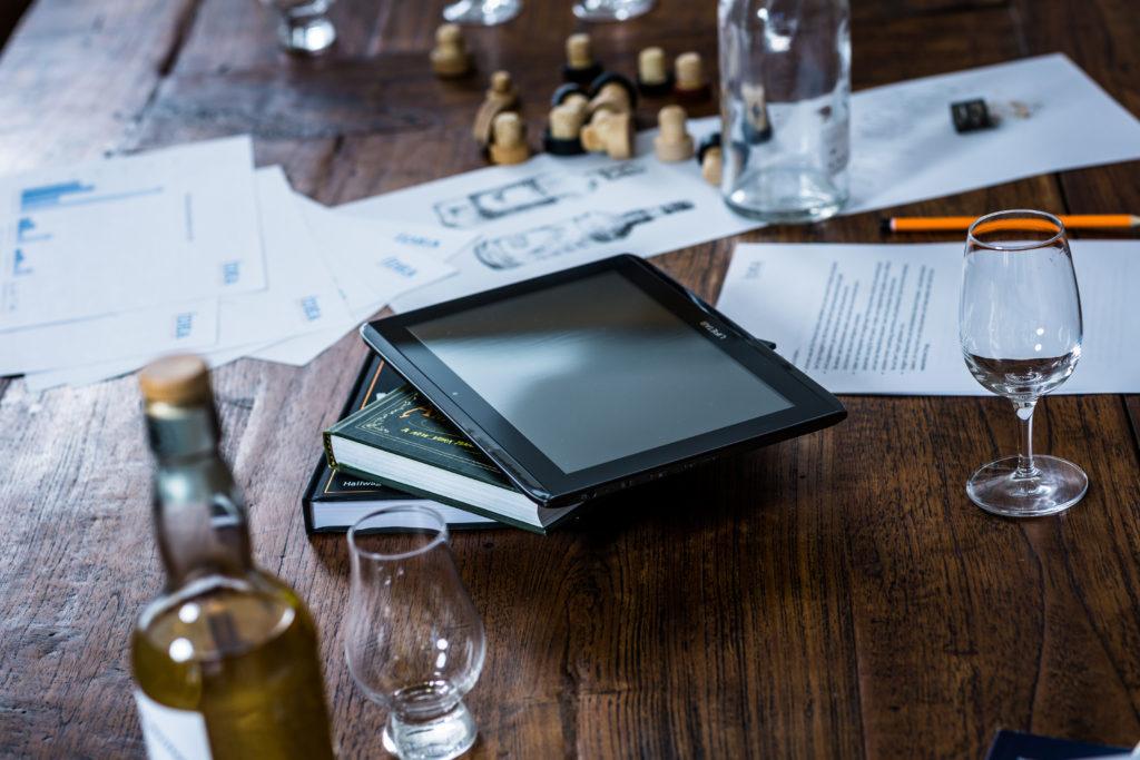 Gläser, Flaschen, Zeichnungen, Korken, ein Stapel Bücher und ein Tablett auf einem Holztisch: Die Idea Distillers beraten zum Thema Social-Media-Marketing (Foto)